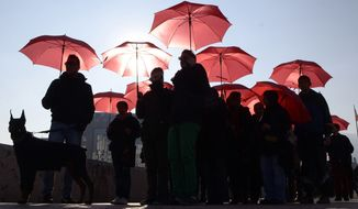 People carrying red umbrellas march through downtown Skopje, Macedonia, marking the International Day to End Violence Against Sex Workers, on Tuesday, Dec. 17, 2013.  A group of sex workers, supported by members of non-government organizations, rallied Tuesday demanding rights for the sex workers and destigmatization of their profession. (AP Photo/Boris Grdanoski/File)