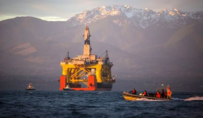With the Olympic Mountains in the background, a small boat crosses in front of an oil drilling rig as it arrives in Port Angeles, Wash., aboard a transport ship after traveling across the Pacific. (Daniella Beccaria/seattlepi.com via Associated Press)