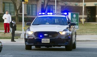 A Fairfax County, Va. police officer leaves Inova Fairfax Hospital Center in Falls Church, Va., Tuesday, March 31, 2015, with emergency lights flashing on his patrol car after a prisoner broke free from his security guard and took his gun. (Associated Press)