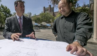 In this Friday, Aug. 7, 2015 photo, Christos Chrysiliou, left, director of architectural and engineering, Los Angeles Unified School District, LAUSD, and Peter Yee, senior project manager, check a Division of the State Architect submittal plan for the mechanical room to be retrofitted at John Marshall High School in Los Angeles. Three years after California voters passed a ballot measure to raise taxes on corporations and generate clean energy jobs by funding energy-efficiency projects in schools, barely one-tenth of the promised jobs have been created. (AP Photo/Damian Dovarganes)