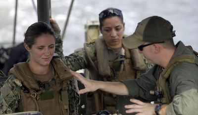 U.S. Navy Master-at-Arms Third Class Danielle Hinchliff, left, and Master-at-Arms Third Class Anna Schnatzmeyer, center, participate in a U.S. Navy Riverine Crewman Course under instructor Boatswain's Mate Second Class Christopher Johnson, right, on a Riverine Assault Boat at Camp Lejeune, N.C.  (AP Photo/Gerry Broome, File)