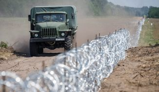 Razor wire marks the border between Hungary and Serbia, but officials are planning to erect a 109-mile-long, 13-foot-tall fence. (Associated Press)