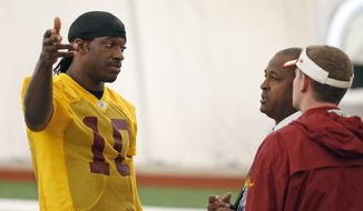 Washington Redskins quarterback Robert Griffin III, left, talks with Tony Wyllie, center, Redskins senior vice president for communications, and Ross Taylor, director of communications, after NFL football practice, Tuesday, Aug. 18, 2015, in Ashburn, Va. Griffin later spoke with reporters. (AP Photo/Alex Brandon)