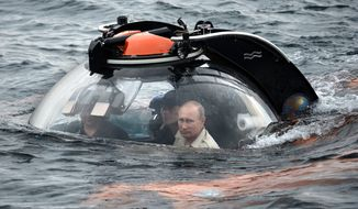Russian President Vladimir Putin, centre, sits on board a bathyscaphe as it plunges into the Black sea along the coast of Sevastopol, Crimea, Tuesday, Aug. 18, 2015. President Vladimir Putin plunged into the Black Sea to see the wreckage of a sunk ancient merchant ship which was found in the end of May. (Alexei Nikolsky/RIA-Novosti, Kremlin Pool Photo via AP)