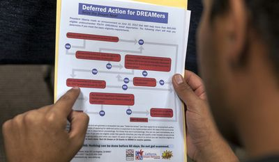 """A legal immigrant reads a guide of the conditions needed to apply for the so-called """"Dreamers"""" program, formally known as Deferred Action for Childhood Arrivals, at the Coalition for Humane Immigrant Rights offices in Los Angeles on Aug. 15, 2012. (Associated Press)"""
