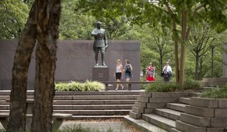 People walk past a statue of Gen. John J. Pershing, who had served as general of the Armies in World War I, in Pershing Park, at 14th Street and Pennsylvania Avenue NW, in Washington, Wednesday, Aug. 19, 2015. (AP Photo/Carolyn Kaster) ** FILE **