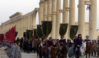 FILE - In this Sept. 27, 2002, file photo, a symbolic trade caravan representing the prosperous trade during the era of Queen Zanobya 260-273AD attend a show held in the ancient city of Palmyra, some 240 kilometers (150 miles) northeast of Damascus, Syria. Islamic State militants beheaded 81-year-old Khaled al-Asaad, a leading Syrian antiquities scholar who spent most of his life looking after the ancient ruins of Palmyra, then hung his body from a pole in a main square of the historic town, Syrian activists and the scholar's relatives said Wednesday, Aug. 19, 2015. (AP Photo/Bassem Tellawi, File)