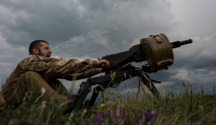 A Ukrainian serviceman fires a weapon at a front line in the eastern Ukrainian village of Krymske. Renewed clashes between the Ukrainian military and rebel forces have grown so intense during recent days that the leaders of France and Germany, who brokered a cease-fire in February, have called for a hastily arranged meeting Monday with Ukraine's pro-Western president. (Associated Press)