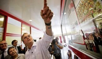 Republican presidential candidate, former Florida Gov. Jeb Bush, right, looks up at photos of celebrities who have visited The Varsity as he arrives at the restaurant for a campaign stop Tuesday, Aug. 18, 2015, in Atlanta. (AP Photo/David Goldman)