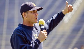 FILE - In this Aug. 6, 2015, file photo, Michigan head coach Jim Harbaugh greets fans in Michigan Stadium during the NCAA college football team's annual media day in Ann Arbor, Mich. It felt at times like Jim Harbaugh's every move was being monitored this offseason, such is the level of excitement and anticipation surrounding his arrival at Michigan. (AP Photo/Tony Ding, File)