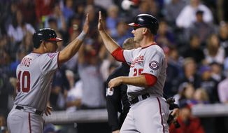 Washington Nationals' Wilson Ramos, left, congratulates Clint Robinson after they scored on a triple by Jayson Werth against the Colorado Rockies during the eighth inning of a baseball game Wednesday, Aug. 19, 2015, in Denver. (AP Photo/David Zalubowski)