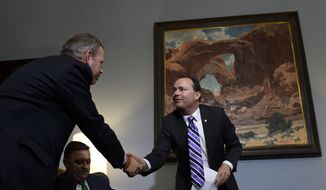 Sen. Mike Lee, R-Utah, right, shakes hands with Dr. Samuel Oliver, president of Union University, left, after participating in a conference call in Lee's Capitol Hill office in Washington, Wednesday, June 3, 2015, with representatives from religious nonprofits who are concerned about how the Supreme Court's upcoming gay marriage decision will affect their institutions, and members of the media. Dr. Jerry Johnson, president of the National Religious Broadcasters is center. (AP Photo/Susan Walsh)