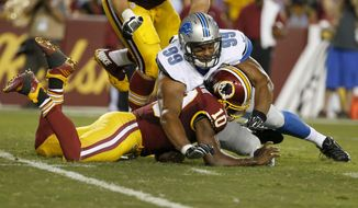 Washington Redskins quarterback Robert Griffin III (10) is hit by Detroit Lions defensive end Corey Wootton (99) while trying to recover a fumble during the first half of an NFL preseason football game, Thursday, Aug. 20, 2015, in Landover, Md. Griffin was injured during the play and left the game. (AP Photo/Alex Brandon)