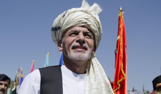 "Afghanistan President Ashraf Ghani listens to the national anthem after putting flowers on the ""Independence Minaret"" monument during an Independence Day ceremony in Kabul, Afghanistan, in this Aug. 19, 2015, file photo. (AP Photo/Massoud Hossaini)"
