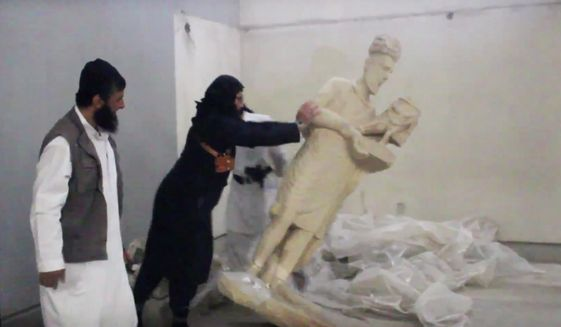 In this image made from video posted on a social media account affiliated with the Islamic State group on Thursday, Feb. 26, 2015, which has been verified and is consistent with other AP reporting, a militant topples an ancient artifact in the Ninevah Museum in Mosul, Iraq. (AP Photo via militant social media account) ** FILE **