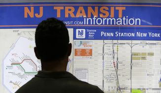 In this July 24, 2015, file photo, a commuter looks over a map of the New Jersey Transit rail lines at Penn Station in New York. (AP Photo/Julie Jacobson, File)