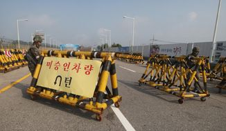 "South Korean army soldiers adjust barricades set up on Unification Bridge, which leads to the demilitarized zone, near the border village of Panmunjom in Paju, South Korea, Saturday, Aug. 22, 2015. The barricade reads: ""Vehicles disapproved."" (AP Photo/Ahn Young-joon)"