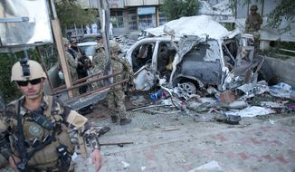 Afghan security forces and British soldiers inspect the site of a suicide attack in the heart of Kabul, Afghanistan, Saturday, Aug. 22, 2015. The suicide car bomber attacked a NATO convoy traveling through a crowded neighborhood in Afghanistan's capital Saturday, killing at least 10 people, including three foreign contractors, authorities said. (AP Photo/Massoud Hossaini