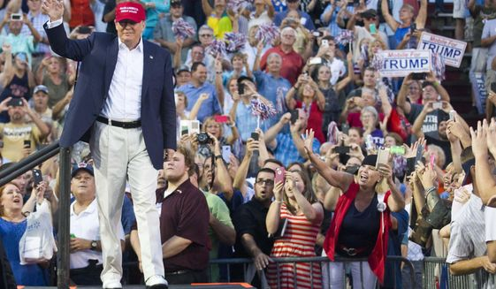 Republican presidential candidate Donald Trump waves to supporters during a campaign rally in Mobile, Ala., on Friday, Aug. 21, 2015. (AP Photo/Brynn Anderson)