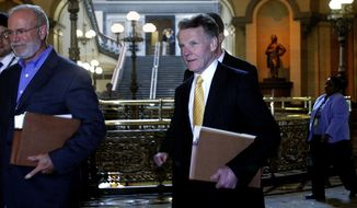 "FILE - In a June, 6, 2007 file photo, Illinois Speaker of the House Michael Madigan's spokesperson Steve Brown, left, walks ahead Madigan, center, past the ""brass rail"" on his way to Illinois Gov. Rod Blagojevich's office at the Illinois State Capitol in Springfield, Ill. Brown is a contract employee with outside clients who depend on Madigan and the Legislature for funding, according to a published report. Brown's clients include a program for nursing assistants that saw its state funding more than double from 2011 to 2013, and a nonprofit group that helps dropouts, which has received $1.6 million in state grants over the past two years, the Chicago Sun-Times reported  (AP Photo/Seth Perlman, File)"