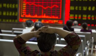 An investor watches a display of stock prices at a brokerage in Beijing. (Associated Press)