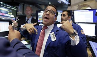Specialist Paul Cosentino (center) works at his post on the floor of the New York Stock Exchange on Aug. 24, 2015. (Associated Press)