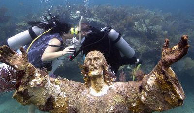 "In this photo provided by the Florida Keys News Bureau, Kimberly Triolet, left, and Jorge Rodriguez, right, kiss after being married next to the Christ of the Deep statue Tuesday, Aug. 25, 2015, in the Florida Keys National Marine Sanctuary off Key Largo, Fla. The wedding helped to mark the 50th anniversary of the installation of the 9-foot-tall bronze sculpture that is a symbol for Key Largo's John Pennekamp Coral Reef State Park, America's first underwater preserve that is part of the sanctuary. It is a replica of the ""Christ of the Abyss"" that was placed in Italian waters in 1954. (Bob Care/Florida Keys News Bureau via AP)"
