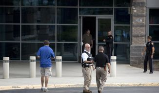 Authorities work at WDBJ's Digital Broadcast Center, Wednesday, Aug. 26, 2015, in Roanoke, Va. Two of the station's journalists were fatally shot while doing an on-air broadcast earlier in the day at Bridgewater Plaza in Moneta, Va. (Erica Yoon/The Roanoke Times via AP)