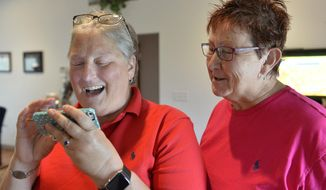 April Miller, left, and her partner Karen Roberts read the decision of the United States Sixth Circuit Court of Appeals refusing to hear Rowan County Clerk Kim Davis' appeal ordering her to issue marriage licenses because of her religious beliefs in Morehead, Ky., Wednesday, Aug. 26, 2015. (AP Photo/Timothy D. Easley)