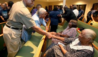 Greater Ebenezer Baptist Church member Michael McDowell, left,  greets fellow member Betty Felder, right,  during a revival, Friday, Aug. 21, 2015, in Waco, Texas. The historically black church  celebrated  its centennial this week with a multi-day revival. (Jerry Larson/Waco Tribune Herald, via AP)