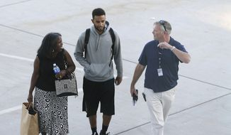 Anthony Sadler, center, who helped stop a terror attack on a high-speed train traveling from Amsterdam to Paris, walks across the tarmac to a waiting vehicle at Sacramento International Airport, Tuesday, Aug. 25, 2015, in Sacramento, Calif. (AP Photo/Rich Pedroncelli)