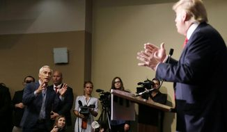 Miami-based Univision anchor Jorge Ramos, left, asks Republican presidential candidate Donald Trump a question about his immigration proposal during a news conference, Tuesday, Aug. 25, 2015, in Dubuque, Iowa. Ramos was later removed from the room. (AP Photo/Charlie Neibergall)