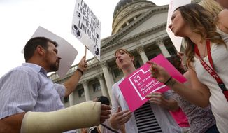 Brandi Jensen, center, shares her opinions with an anti-Planned Parenthood protester as Planned Parenthood Action Council holds a community rally at the state Capitol in Salt Lake City on Aug. 25, 2015. Planned Parenthood Association of Utah CEO Karrie Galloway says the demonstration is a protest against Gov. Gary Herbert's decision to stop disbursing federal money to Planned Parenthood. (Leah Hogsten/The Salt Lake Tribune via AP) **FILE**