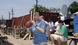 FILE - In this May 10, 2007, file photo, New Orleans Saints quarterback Drew Brees throws a football to some of the workers that took a break while working on a Habitat for Humanity home in the Musicians Village in the Ninth Ward of  New Orleans. Drew Brees had little choice but to sign with a downtrodden franchise in an epic disaster zone in the spring of 2006. Yet, in the decade since Hurricane Katrina laid waste to much of New Orleans, it has become apparent to the record-setting quarterback that the timing of his career-threating, throwing-shoulder injury, which left him with no better option than to become a Saint, could not have been better. (AP Photo/Bill Haber, File)