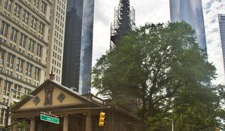 """In this June 25, 2015, file photo, the World Trade Center, right, looms behind St. Paul's Chapel with its steeple wrapped in scaffolding for repairs, in New York. The winner of a new competition open to people of all faiths, called """"The Reconciliation Preaching Prize,"""" has been won by an Army chaplain from Austin, Texas. The Rev. David Peters will have the privilege of delivering an original sermon on Sept. 11, at the chapel near ground zero that was turned into a makeshift memorial shrine and became a place of rest and renewal for volunteers and responders, following the terrorist attacks that brought down the twin towers. (AP Photo/Bebeto Matthews, File)"""