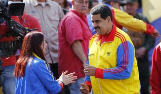 Venezuela's President Nicolas Maduro dances with first lady Cilia Flores during a rally to support the closing of the Colombian border, in Caracas, Venezuela, Friday, Aug. 28, 2015. President Maduro announced that he would extend the week-old partial closure of the border with Colombia to more cities and send additional troops to the area, doubling down on a policy has drawn rebuke by Colombian leaders. (AP Photo/Ariana Cubillos) **FILE**