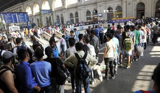 Migrants queue to buy ticket for a train to Munich, Germany at the Keleti Railway Station in Budapest, Hungary, Monday, Aug. 31, 2015. Migrants possessing valid documents and a train ticket are being  allowed on international trains at the station.  (Tamas Kovacs/MTI via AP)