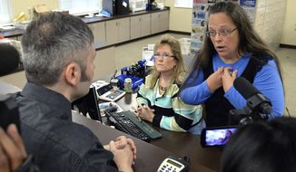 Rowan County Clerk Kim Davis, right, talks with David Moore following her office's refusal to issue marriage licenses at the Rowan County Courthouse in Morehead, Ky., Tuesday, Sept. 1, 2015. (AP Photo/Timothy D. Easley)
