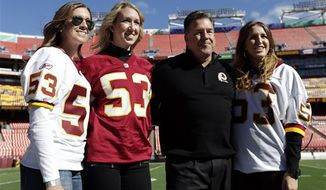 Ashley Bostic, left, Amanda Bostic, and Alicia Bostic, right, pose on the field with their father former Washington Redskin Jeff Bostic before an NFL football game against the Tennessee Titans, Sunday, Oct. 19, 2014, in Landover, Md. (AP Photo/Mark E. Tenally)