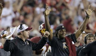 Washington Redskins head coach Jay Gruden and quarterback Robert Griffin III, right, celebrate running back Mack Brown's touchdown during the second half of an NFL preseason football game against the Jacksonville Jaguars in Landover, Md., Thursday, Sept. 3, 2015. (AP Photo/Mark Tenally)