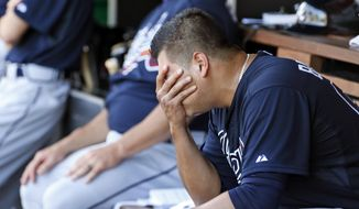 Atlanta Braves starting pitcher Manny Banuelos holds his face in this hand after he was relieved during the third inning of a baseball game against the Washington Nationals at Nationals Park, Sunday, Sept. 6, 2015, in Washington. (AP Photo/Alex Brandon)