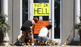 Women place a sign outside Dr. Walter James Palmer's dental office in Bloomington, Minn., on July 29, 2015. Mr. Palmer reportedly paid $50,000 to track and kill Cecil, a black-maned lion, just outside Hwange National Park in Zimbabwe. (Associated Press)