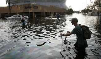 This Aug, 31, 2005, file photo shows a man pushing his bicycle through flood waters near the Superdome in  New Orleans after Hurricane Katrina left much of the city underwater. (AP Photo/Eric Gay, File)