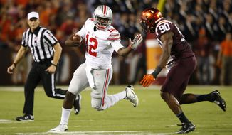 Ohio State quarterback Cardale Jones (12) trees to get past Virginia Tech defensive end Dadi Lhomme Nicolas (90) during the first half of an NCAA college football game in Blacksburg, Va., Monday, Sept. 7, 2015. (AP Photo/Steve Helber)
