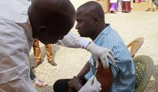 A health worker injects a man with an Ebola vaccine in Conakry, Guinea, on March 7. (Associated Press)