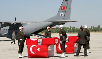 Turkish soldiers prepare the coffins of fallen comrades, including Lt. Col. Ilker Celikcan, front, before a ceremony at the military airport in Van, Turkey, Tuesday, Sept. 8, 2015, two days after 16 soldiers were killed and six others were wounded in a Kurdish rebel attack against troops in southeast Turkey on Sunday. The attack was the deadliest assault on Turkish troops since renewed fighting between the rebels and Turkey's security forces erupted in July, shattering a fragile peace process. (IHA Agency via AP)