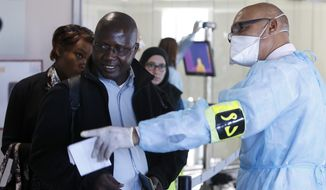 A worker from a Moroccan health screening team dressed in protective gear directs passengers at the arrivals hall of the Mohammed V airport in Casablanca on Oct 9. (Associated Press)