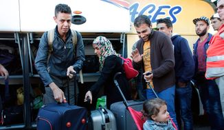Wissam Ahmed, from Iraq, left, and other refugees arrive after an overnight bus trip from Germany, in Champagne-sur-Seine, south of Paris, France, Wednesday, Sept. 9, 2015, the first among around 1,000 that French President Francois Hollande pledged to receive from the neighboring country. (AP Photo/Thibault Camus)