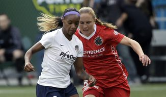 Washington Spirit defender Crystal Dunn, left, takes the ball downfield against Portland Thorns defender Rachel Van Hollebeke during the first half of an NWSL soccer match in Portland, Ore., Sunday, Aug. 30, 2015. The teams tied 3-3. (AP Photo/Don Ryan)