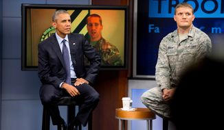 President Barack Obama, accompanied by Tech Sgt. Nathan Parry, right, takes a question from a service member in Afghanistan, on screen at center, during a town hall with service members at Fort Meade, Md., Friday, Sept. 11, 2015, on the 14th anniversary of the 9/11 attacks. (AP Photo/Andrew Harnik)
